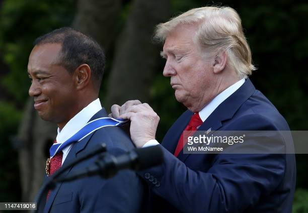 S President Donald Trump presents professional golfer and business partner Tiger Woods with the Medal of Freedom during a ceremony in the Rose Garden...