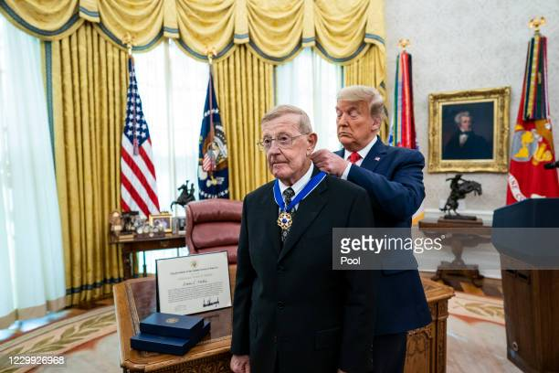 President Donald Trump presents the Medal of Freedom to former college football coach Lou Holtz in the Oval Office of the White House on December 3,...