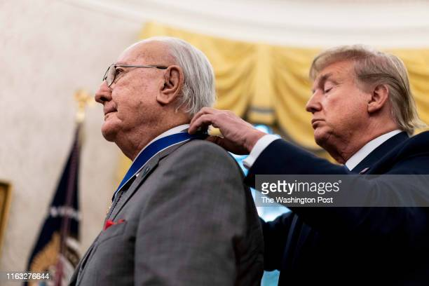 President Donald Trump presents the Presidential Medal of Freedom to former basketball player Robert Cousy in the Oval Office at the White House in...