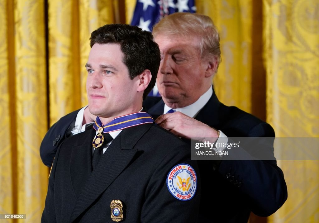 US President Donald Trump presents the Public Safety Medal of Valor Award to Emergency Medical Technician Sean Ochsenbein (L) from Putnam County, Tennessee, Rescue Squad, during a ceremony in the E...