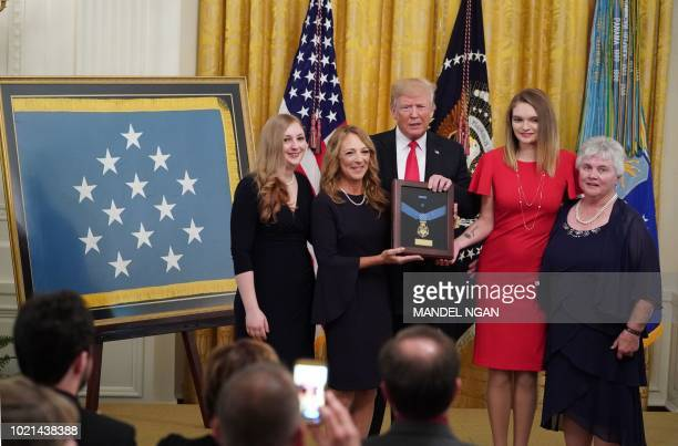 US President Donald Trump presents Valerie Nessel the widow of Air Force Tech Sgt John Chapman with his Medal of Honor during a ceremony in the East...
