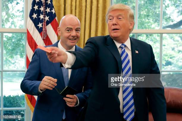 S President Donald Trump pretends to give a red card to members of the news media with FIFA President Gianni Infantino in the Oval Office at the...