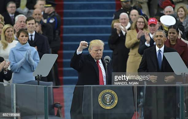 US President Donald Trump pumps his fist after addressing the crowd during his swearingin ceremony on January 20 2017 at the US Capitol in Washington...
