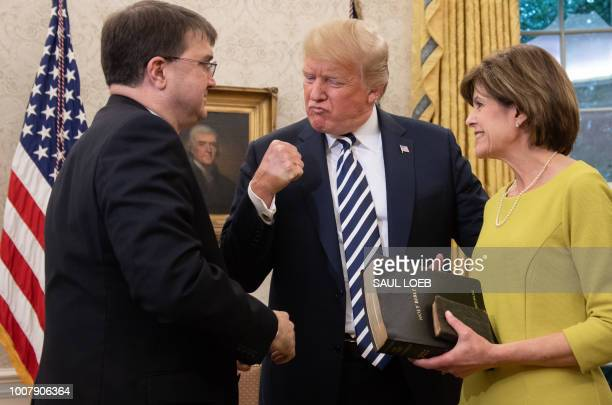 US President Donald Trump pumps his fist alongside Robert Wilkie after he was swornin as Secretary of Veterans Affairs alongside his wife Julia in...