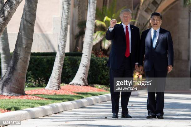 President Donald Trump pumps his fist as he and Chinese President Xi Jinping walk together at the MaraLago estate in West Palm Beach Florida April 7...