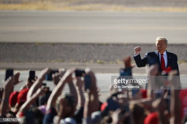 President Donald Trump pumps his fist as he arrives for a campaign rally at Phoenix Goodyear Airport October 28, 2020 in Goodyear, Arizona. With less...
