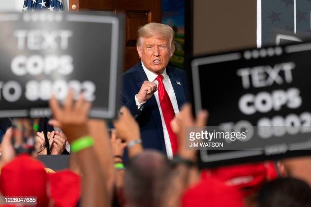 President Donald Trump pumps his fist as he delivers remarks to the City of New York Police Benevolent Association at the Trump National Golf Club in...