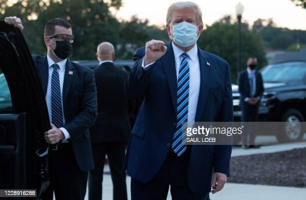 President Donald Trump pumps his fist as he leaves Walter Reed Medical Center in Bethesda, Maryland heading towards Marine One on October 5 to return...