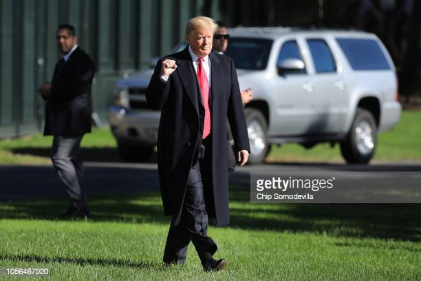 S President Donald Trump pumps his fist as he walks across the South Lawn before boarding Marine One and departing the White House October 18 2018 in...