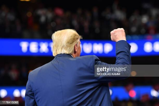 """President Donald Trump pumps his fist during a """"Keep America Great"""" rally at the American Airlines Center in Dallas, Texas on October 17, 2019."""