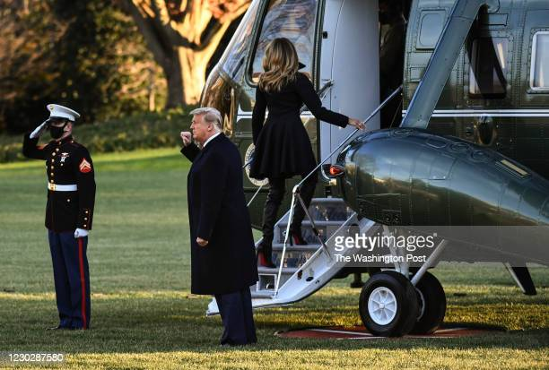 President Donald Trump p[ups his first towards supporters as First Lady Melania Trump boards Marine One on the South Lawn of the White House on their...