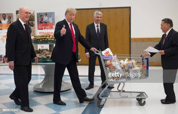 President Donald Trump pushes a shopping cart as he tours the Church of Jesus Christ of Latter-Day Saints' food distribution center at LDS Welfare...