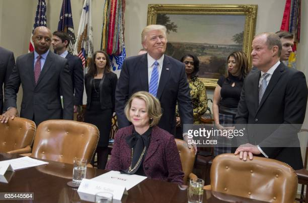 US President Donald Trump pushes in the chair for Jill Soltau CEO of JoAnn stores alongside Art Peck CEO of Gap Inc and Marvin Ellison CEO of J C...