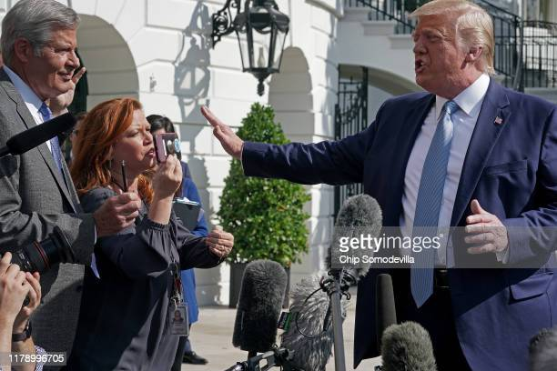 President Donald Trump puts his hand in front of NBC News' Kelly O'Donnell as he answers journalists' questions on the South Lawn before boarding...