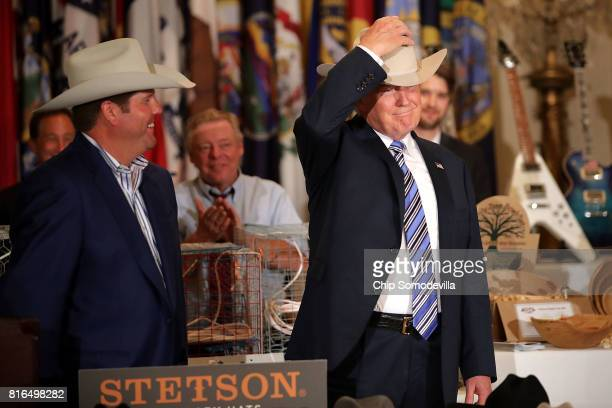 S President Donald Trump puts on a Stetson cowboy hat while touring a Made in America product showcase in the East Room of the White House July 17...