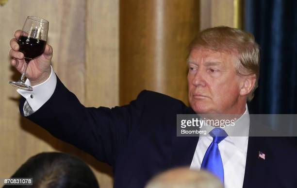 US President Donald Trump raises a wine glass as he toasts after delivering a speech during a state banquet at Akasaka Palace in Tokyo Japan on...