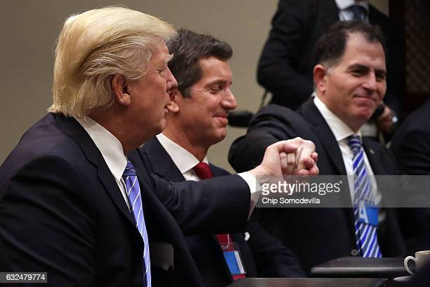 S President Donald Trump reaches across Alex Gorsky of Johnson Johnson to shake hands with Michael Dell of Dell Technologies after saying his...