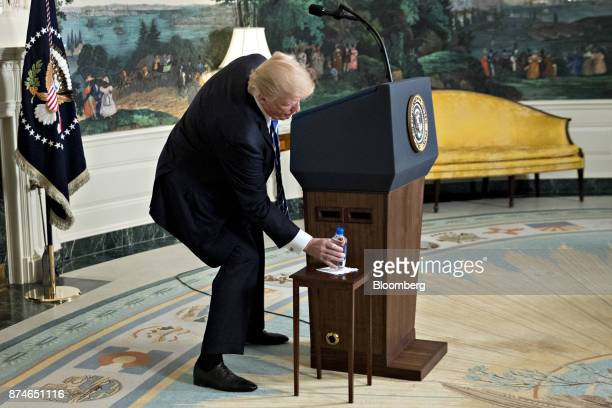 US President Donald Trump reaches for a bottle of water while delivering remarks on his recent 11day Asia trip in the Diplomatic Room of the White...