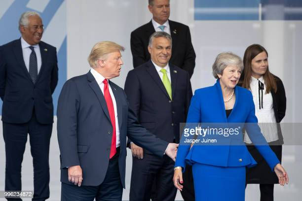President Donald Trump reaches out to British Prime Minister Theresa May at the 2018 NATO Summit at NATO headquarters on July 11 2018 in Brussels...
