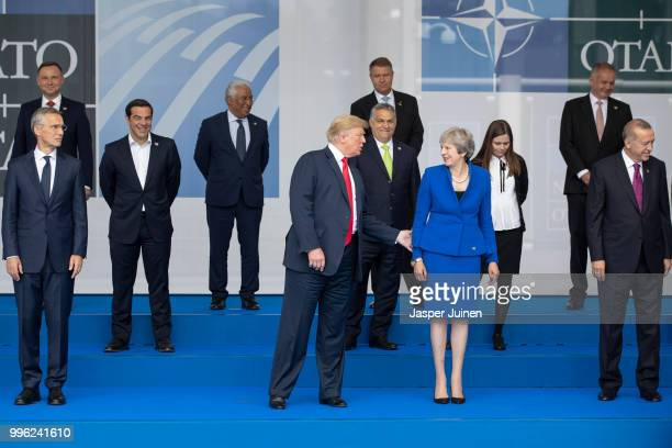 President Donald Trump reaches out to British Prime Minister Theresa May at the photo call at the 2018 NATO Summit at NATO headquarters on July 11...