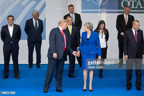 President Donald Trump reaches out to British Prime Minister Theresa May 2018 NATO Summit at NATO headquarters on July 11 2018 in Brussels Belgium...