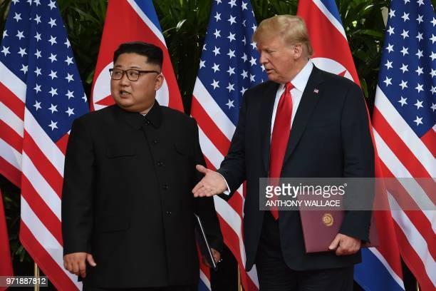 US President Donald Trump reaches out to shake hands with North Korea's leader Kim Jong Un in front of the media after taking part in a signing...