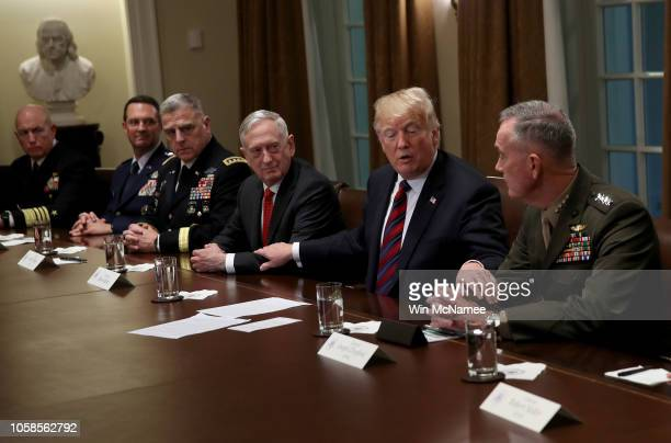 S President Donald Trump reaches out to touch the arms of Chairman of the Joint Chiefs of Staff Joseph Dunford and US Defense Secretary Jim Mattis...