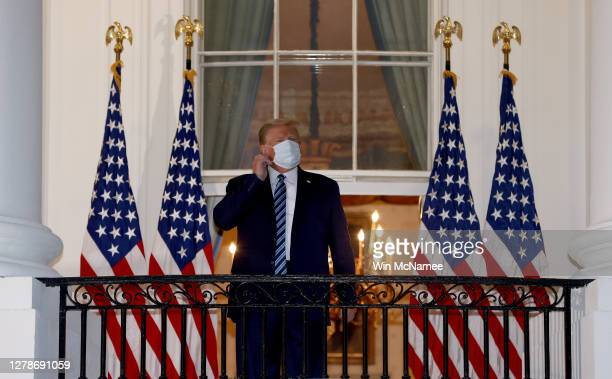 President Donald Trump reaches to remove his mask upon return to the White House from Walter Reed National Military Medical Center on October 05,...