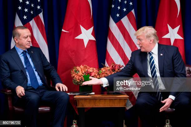 US President Donald Trump reaches to shake Turkey's President Recep Tayyip Erdogan's hand before a meeting at the Palace Hotel during the 72nd United...