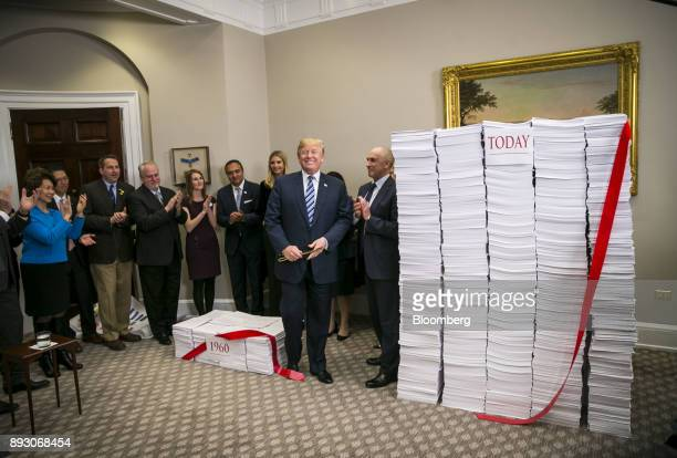US President Donald Trump reacts after cutting red ribbon between two stacks of paper representing the regulatory code from 1960 compared to today...