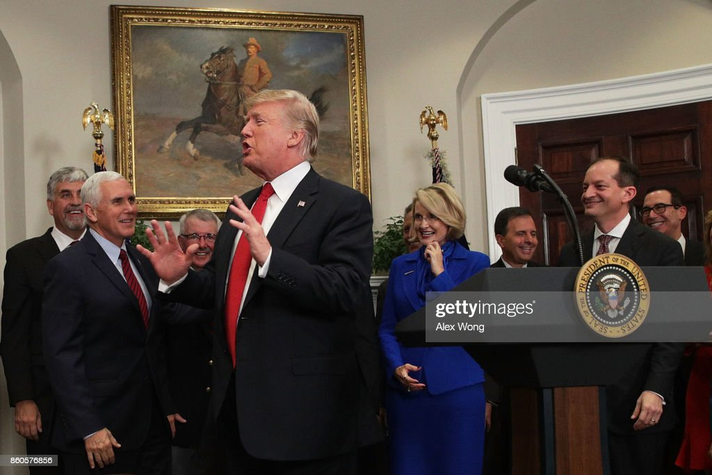U.S. President Donald Trump reacts after he forgot and was reminded to sign an executive order as Vice President Mike Pence (2nd L), Secretary of the Treasury Steven Mnuchin (R) and Secretary of Labor Alexander Acosta (2nd R) look on during an event in the Roosevelt Room of the White House October 12, 2017 in Washington, DC. President Trump signed the executive order to loosen restrictions on Affordable Care Act 'to promote healthcare choice and competition.'