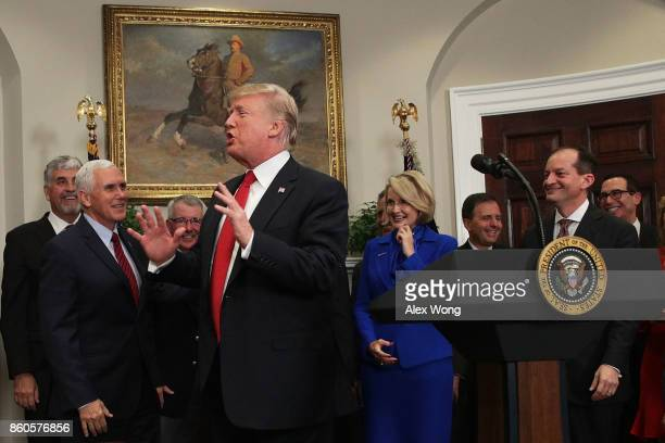 S President Donald Trump reacts after he forgot and was reminded to sign an executive order as Vice President Mike Pence Secretary of the Treasury...