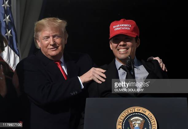 US President Donald Trump reacts as Nationals player Kurt Suzuki wears a Make America Great Again baseball hat during a ceremony to welcome the 2019...