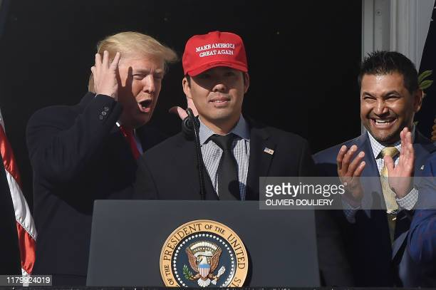 US President Donald Trump reacts as player Kurt Suzuki wears a Make America Great Again baseball hat during a ceremony to welcome the 2019 World...