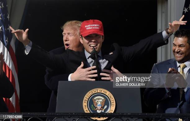 President Donald Trump reacts as player Kurt Suzuki wears a Make America Great Again baseball hat during a ceremony to welcome the 2019 World Series...