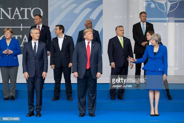 President Donald Trump reacts to British Prime Minister Theresa May while standing beside NATO Secretary General Jens Stoltenberg at the 2018 NATO...