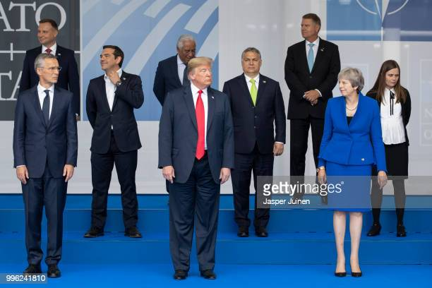 President Donald Trump reacts to British Prime Minister Theresa May at the photo call at the 2018 NATO Summit at NATO headquarters on July 11 2018 in...