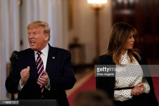S President Donald Trump reacts while standing next to First Lady Melania Trump after speaking in the East Room of the White House one day after the...