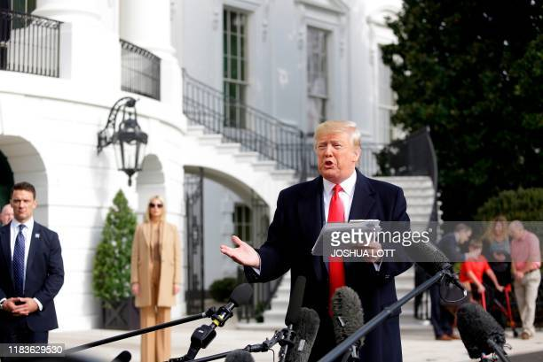 US President Donald Trump reads from his notes as he talks to the media on the South Lawn of the White House before boarding Marine One in Washington...