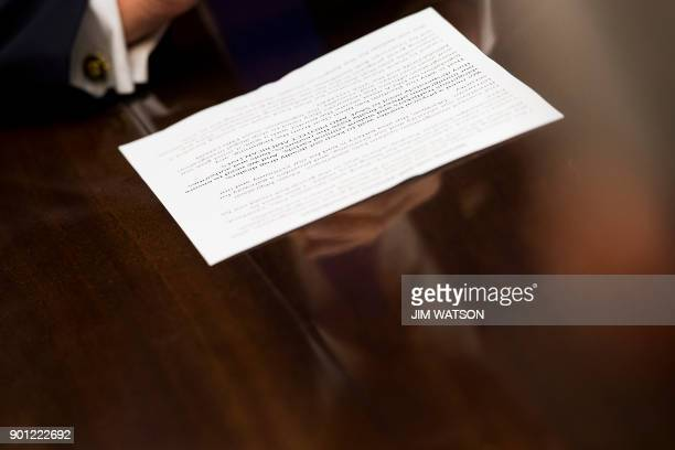 US President Donald Trump reads from his notes that say We need a physical border wall during a meeting with Republican members of the Senate about...
