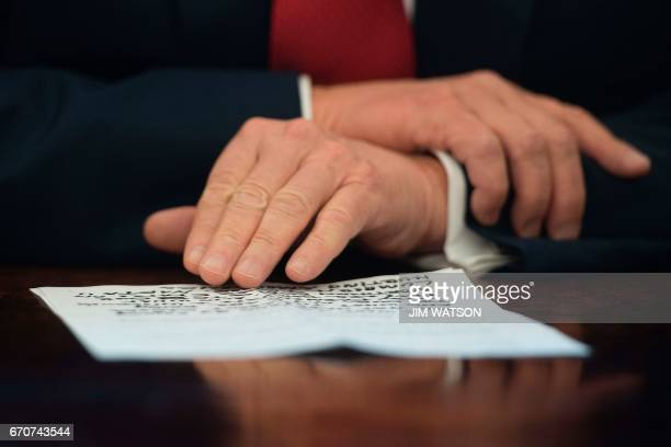 US President Donald Trump reads from notes before signing the Memorandum Regarding the Investigation Pursuant to Section 232 of the Trade Expansion...