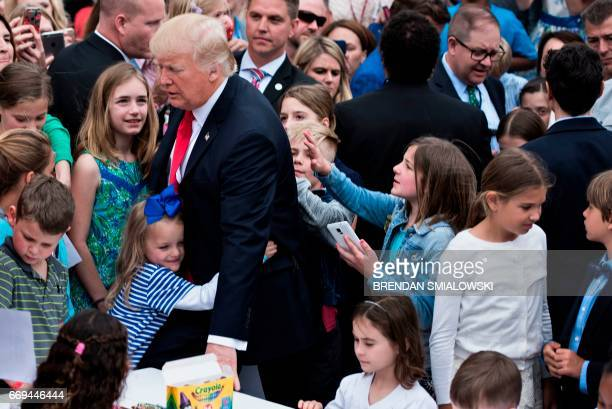 US President Donald Trump receives a hug during the Easter Egg Roll on the South Lawn of the White House April 17 2017 in Washington DC / AFP PHOTO /...