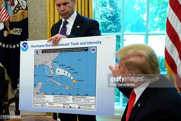 President Donald Trump references a map held by acting Homeland Security Secretary Kevin McAleenan while talking to reporters following a briefing...
