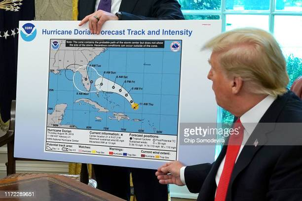 S President Donald Trump references a map held by acting Homeland Security Secretary Kevin McAleenan while talking to reporters following a briefing...
