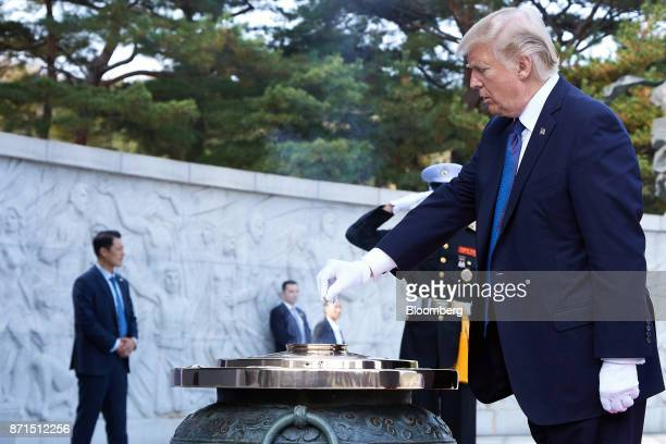 US President Donald Trump releases incense into a large ceremonial urn during a wreathlaying ceremony at the National Cemetery in Seoul South Korea...