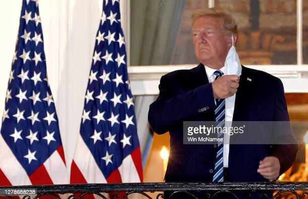 S President Donald Trump removes his mask upon return to the White House from Walter Reed National Military Medical Center on October 05 2020 in...