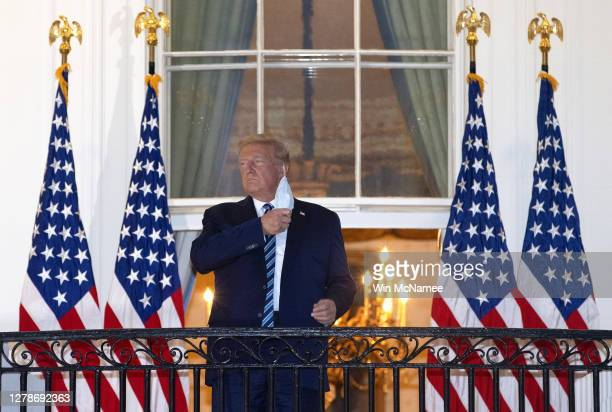 President Donald Trump removes his mask upon return to the White House from Walter Reed National Military Medical Center on October 05, 2020 in...