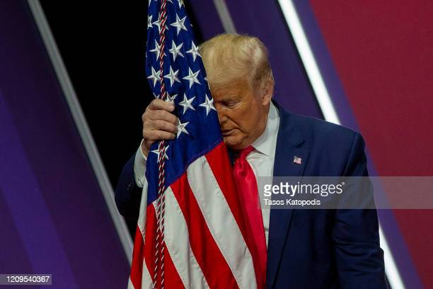 President Donald Trump rests his head on the flag of the United States of America at the annual Conservative Political Action Conference at Gaylord...