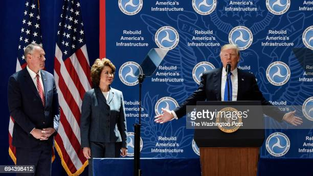 President Donald Trump right addresses a gathering at the Department of Transportation with Secretary Elaine Chao center and Secretary Ryan Zinke...