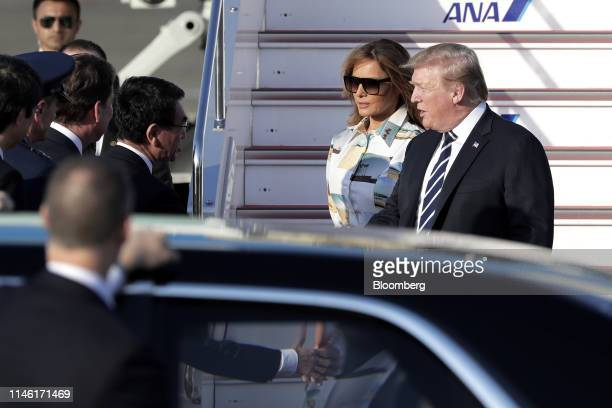 US President Donald Trump right and First Lady Melania Trump second right are greeted by Taro Kono Japan's foreign minister after disembarking from...